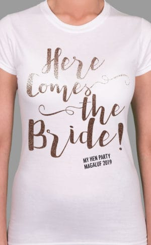 Image to buy product Here Comes The Bride Glitter Personalised Hen Party T Shirt. A bride's version of the design in script lettering in glitter rose gold print with subtext in black on a white lady fit t-shirt.
