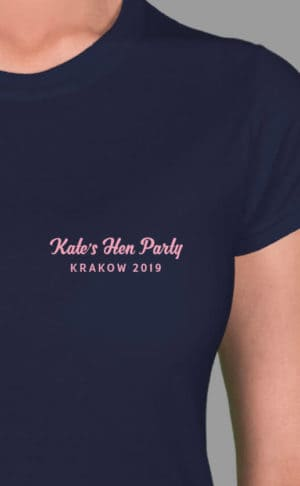 Image to buy product Minimal Script - Top Left Personalised Hen Party T Shirt. Script and bold fonts in baby pink print on a navy lady fit t-shirt.