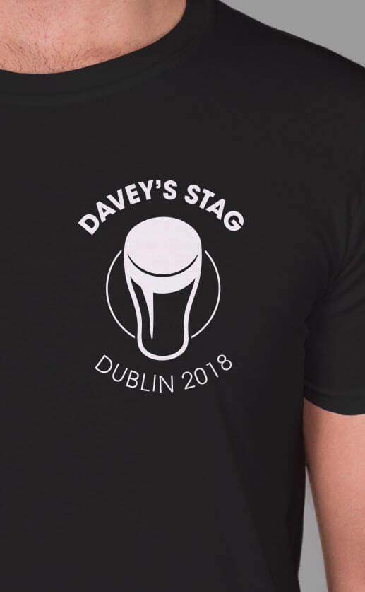 Graphic silhouette illustration of a pint. Small top left design with personalised text over the top and underneath. White print on a black t-shirt