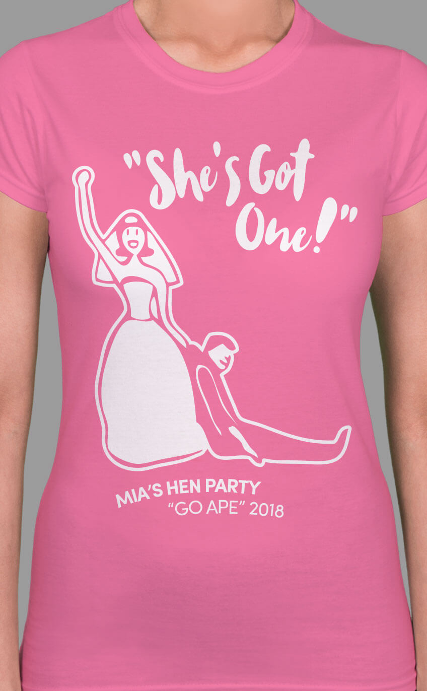 Image to buy product She's Got One! Personalised Hen Party T Shirt. Stylised graphic of bride holding a groom with script lettering in white print on a azalea lady fit t-shirt.