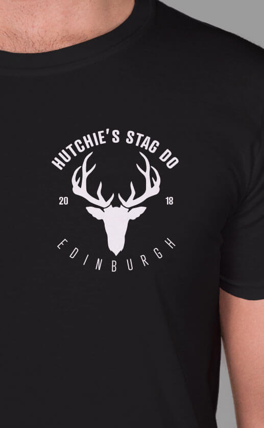 Small top left graphic of a stag silhouette with horns. Personalised text around and under design. White print on black t-shirt.